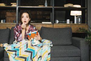 femme assise canapé TV